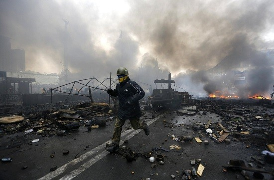 An anti-government protester runs trough the rubble after violence erupted in Ukraine protests