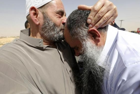 Radical Muslim cleric Abu Qatada (R) reacts as his father kisses his head after he was released from a prison near Amman September 24, 2014.