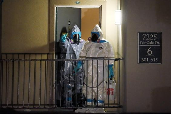 Workers in hazardous material suits step out of an apartment unit where a man diagnosed with the Ebola virus was staying in Dallas, Texas, October 5, 2014.