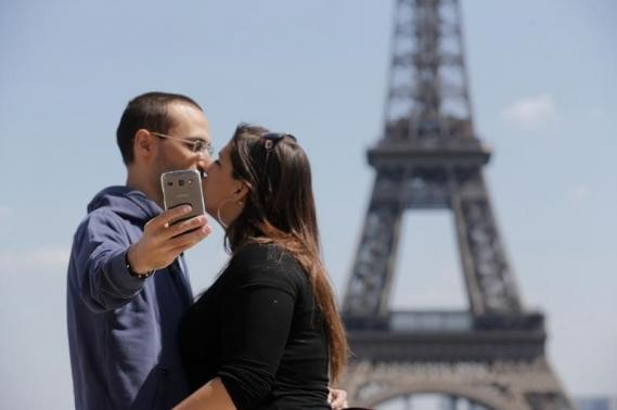 A couple of tourists use a mobile phone to take a selfie picture as they kiss at the Trocadero Square near the Eiffel Tower in Paris, May 16, 2014.