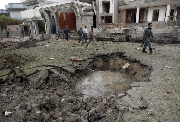 Afghan policemen walk near a crater at the site of a suicide attack at the Indian consulate in Jalalabad province August 3 2013