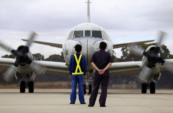 "Aircraft technicians from the Japan Maritime Self-Defense Force. Malaysia's Transport Ministry said the final voice transmission from the plane's cockpit of Flight 370 was actually ""Good night Malaysian three seven zero."""
