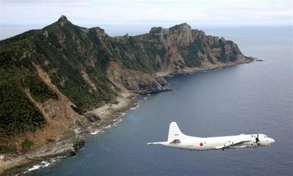 Japan Maritime Self-Defense Force's PC3 surveillance plane flies around the disputed islands in the East China Sea, known as the Senkaku isles in Japan and Diaoyu in China, in this October 13, 2011 file photo.