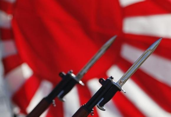 Bayonets attached to rifles used by Japanese Self-Defense Forces are seen in front of Japan's rising sun flag, which is used by the forces, during the annual troop review ceremony at Asaka Base in Asaka, near Tokyo October 27, 2013.