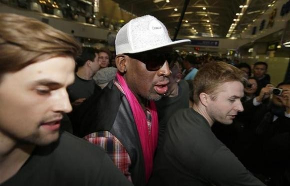 Former NBA basketball player Dennis Rodman (C) is protected by staff members as he arrives at the Beijing Capital International Airport to leave for Pyongyang, in Beijing, January 6, 2014.
