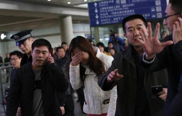 A Relative of a Passenger Onboard Malaysia Airlines Flight MH370, Covers Her Face as She Cries at the Beijing Capital International Airport in Beijing March 8, 2014