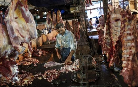 A butcher cuts up portions of beef for sale in an abattoir at a wholesale market in Mumbai (Reuters)