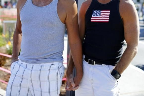 A gay couple hold hands during a rally in support of the United States Supreme Court