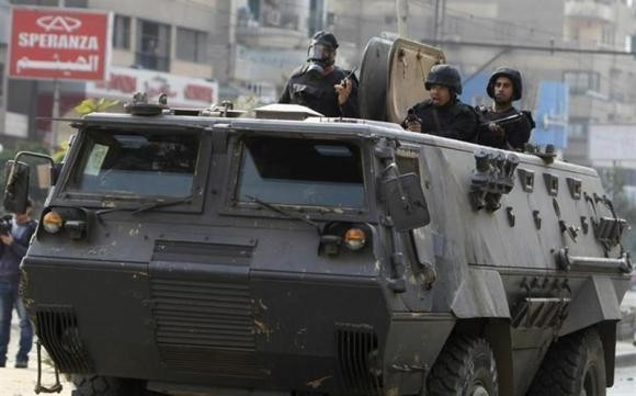 Riot police look from their armoured personnel vehicle during clashes with supporters of Muslim Brotherhood and ousted Egyptian President Mohamed Mursi at Nasr City district in Cairo, January 3, 2014.