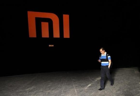 A man walking past Xiaomi logo