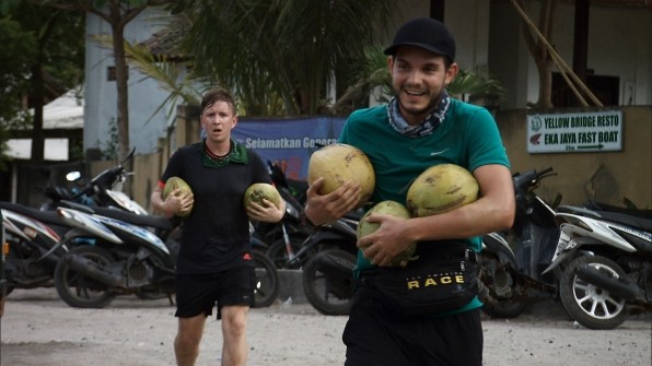Tyler and Korey carrying coconuts during a task