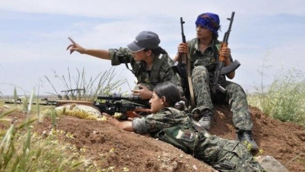 A Kurdish Woman's Protection Unit,YPJ sniper takes position on a hill,while her colleagues watch on.