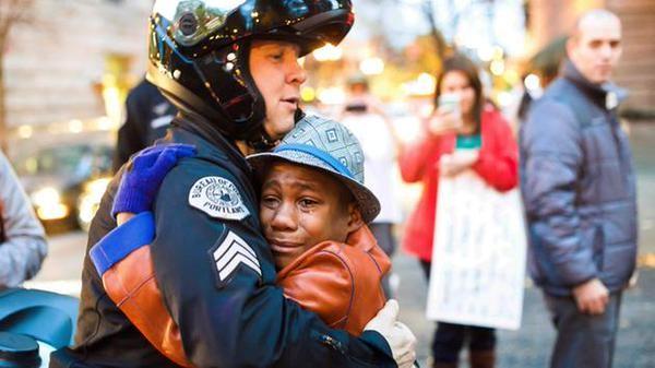 White Cop Hugging Black Boy