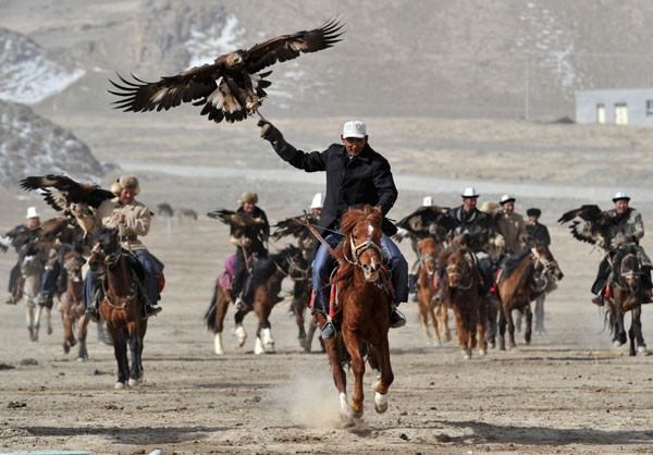 Herdsmen from the Kyrgyz ethnic group hold their falcons as they ride on horses during a performance to celebrate the Nowruz festival