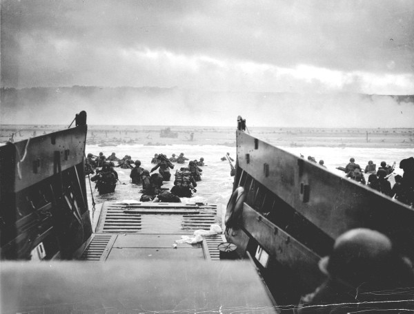 US troops wade ashore from a Coast Guard landing craft at Omaha Beach during the Normandy