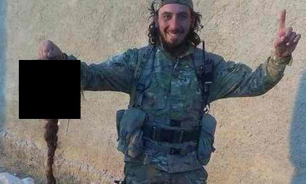 An ISIS militant posing with the head of a captured Kurdish female fighter