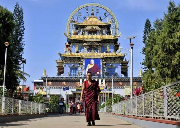 A Tibetan Buddhist monk walks in front of the Golden Temple inside the Nyingmapa Monastery in Bylakuppe, southwest of Bengaluru, previously known as Bangalore, December 4, 2014.