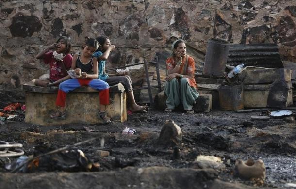 A family sits amid the burnt debris of their hut.