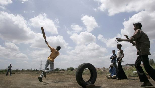 Children play cricket against the backdrop of monsoon clouds in Ahmedabad,