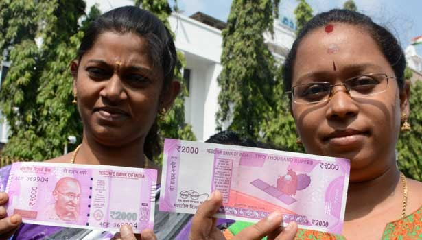 Women pose with the new Rs 2000 note.
