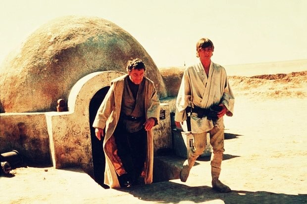 Luke Skywalker pictured with his uncle coming out of their house in 1977's Star Wars