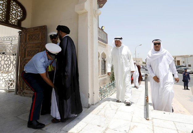 A police officer frisks a man arriving for Friday prayers at the Al A'ali Grand Mosque in Al A'ali south of Manama, July 3, 2015.