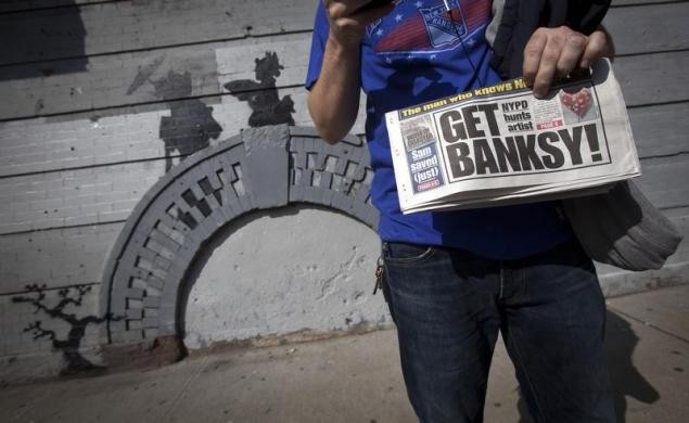 A man holds up a local newspaper in front of an art piece by British street artist Banksy in New York.
