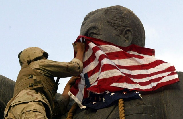 A U.S. Marine covers the face of a statue of Iraqi President Saddam Hussein with a U.S. flag in Baghdad, on April 9, 2003. U.S. troops briefly draped an American flag over the face of a giant statue of Hussein, as they prepared to topple it in front of a