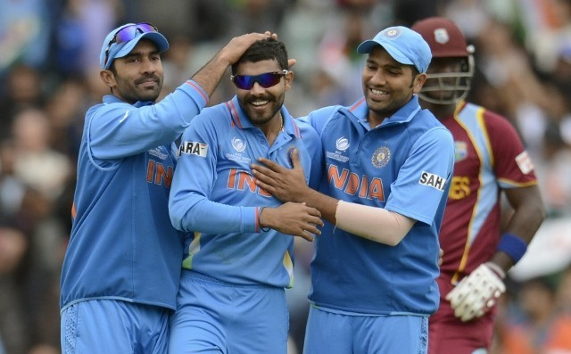 India spinner Ravindra Jadeja is congratulated by Dinesh Karthik and Rohit Sharma after picking up the wicket of West Indies batsman Ravi Rampaul in their ICC Champions Trophy 2013 game. Reuters