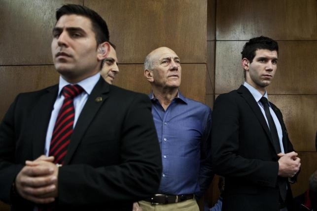 Former Israeli Prime Minister Ehud Olmert (2nd R) waits to hear his verdict at the Tel Aviv District Court March 31, 2014.