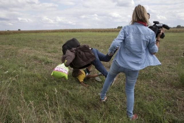 A migrant carrying a child falls after being tripped by TV camerawoman (R) Petra Laszlo while trying to escape from a collection point in Roszke village, Hungary, September 8, 2015. REUTERS/MARKO DJURICA