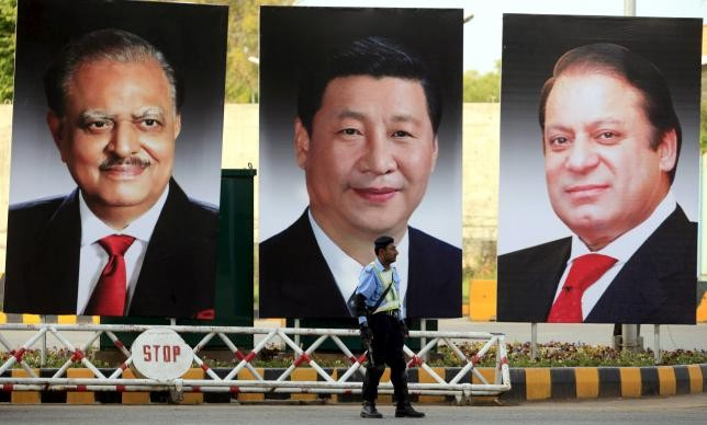A policeman stands guard next to giant portraits of (L-R) Pakistan's President Mamnoon Hussain, China's President Xi Jinping, and Pakistan's Prime Minister Nawaz Sharif, displayed along a road ahead of Xi's visit to Islamabad April 19, 2015
