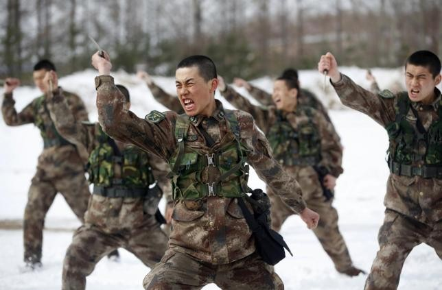 People's Liberation Army (PLA) soldiers shout as they practise with knives during a training
