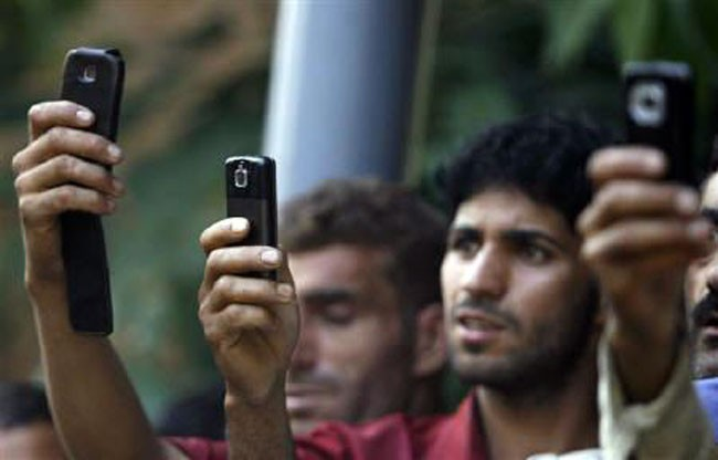 Kashmiri youth use their mobile phones to take pictures during the funeral of Feroz Ahmad Malik in Palhalan, north of Srinagar September 6, 2010