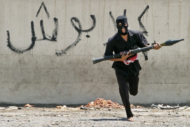 :A masked Iraqi Shi'ite militiaman with a rocket-propelled grenade launcher