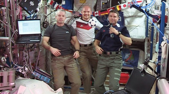 """(From left) Expedition 40 Commander Steve Swanson and Flight Engineers Alexander Gerst and Reid Wiseman wish soccer fans and the World Cup 2014 """"peaceful games."""" (NASA TV)"""