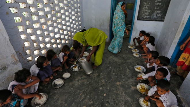 A cook serves the free mid-day meal, distributed by a government-run primary school
