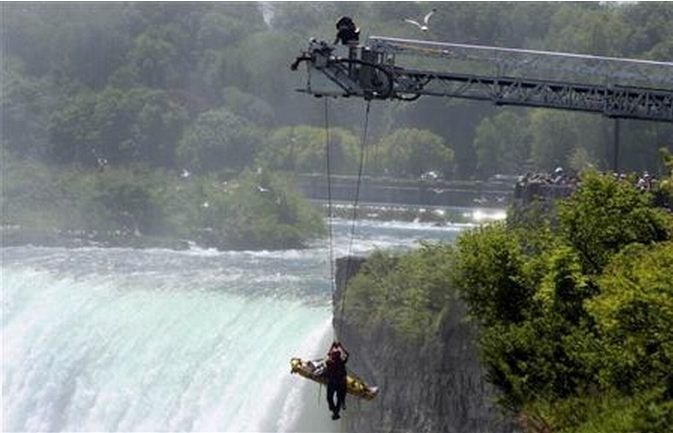 Niagara Falls firefighter Matt Rozon and an unidentified man are lifted from the Niagara gorge by an aerial fire truck in Niagara Falls May 21, 2012.