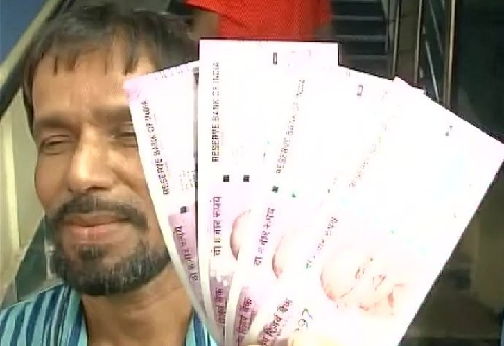 Man poses with the new Rs 2000 note.