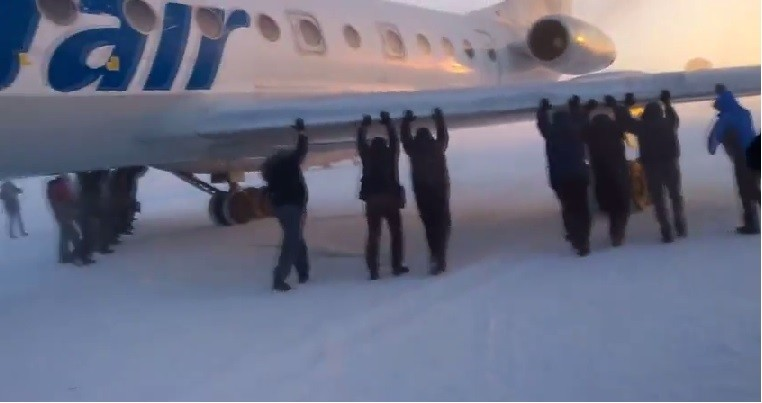 Siberia air passengers had to get out and push their plane stuck in snow