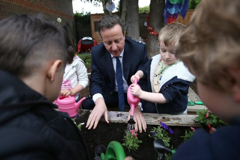 Prime Minister David Cameron plants flowers with children,Prime Minister David Cameron,David Cameron,Britain's Prime Minister David Cameron plants flowers,children's nursery,children nursery,Priti Patel