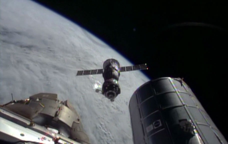The Soyuz TMA-11M spacecraft backs away from the International Space Station shortly after undocking. (NASA TV)