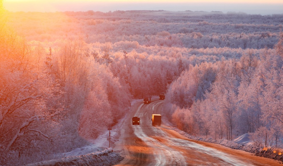 Vehicles drive during sunrise in the Taiga area along the M54 Krasnoyarsk – Mongolia highway, with the air temperature at about – 27 degrees C (-16.6 degrees F), some 120 km (75 mi) south of Russia's Siberian city of Krasnoyarsk, on December 14, 2011.