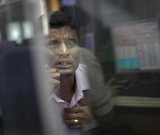 a-broker-looks-at-a-computer-screen-as-he-talks-on-a-phone-at-a-stock-brokerage-firm-in-mumbai-december-3-2012