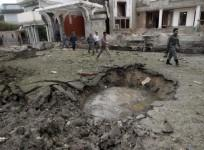 Afghan policemen walk near a crater at the site of a suicide attack at the Indian consulate in Jalalabad province August 3 2013.