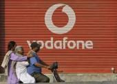 a-man-and-two-passengers-ride-on-a-scooter-past-a-shop-displaying-the-vodafone-logo-on-its-shutter-in-jammu