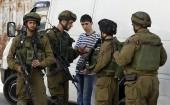 Israeli soldiers search a Palestinian youth during an operation to locate three Israeli teens in the West Bank city of Hebron June 16 2014.