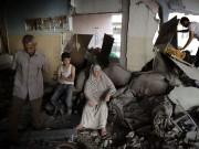 A Palestinian family gathers inside their damaged home, which police said was targeted in an Israeli air strike, in Gaza City.