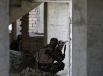 Afghan security personnel take position at the site of an attack, opposite a building where unidentified militants are located at, north of Kabul International Airport in Kabul