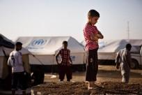 A boy, who fled from the violence in Mosul, stands near tents in a camp for internally displaced people on the outskirts of Arbil in Iraq's Kurdistan region